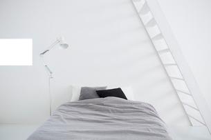 白い壁と白い床の空間にあるベッドルームの写真素材 [FYI03816008]