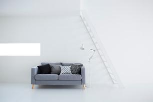 白い壁と白い床の空間にあるグレーのソファの写真素材 [FYI03816009]