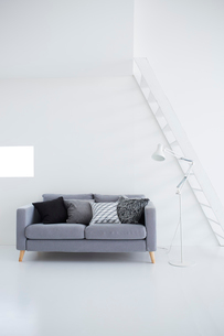 白い壁と白い床の空間にあるグレーのソファの写真素材 [FYI03816010]