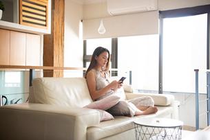 リビングのソファに座ってスマホを触っている女性の写真素材 [FYI03816425]