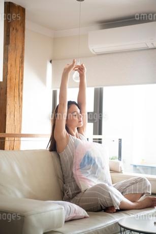 ソファに座ってストレッチをしている女性の写真素材 [FYI03816429]