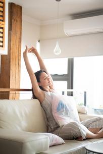 ソファに座ってストレッチをしている女性の写真素材 [FYI03816460]