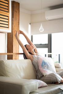 ソファに座ってストレッチをしている女性の写真素材 [FYI03816463]