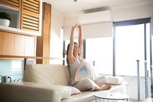 ソファに座ってストレッチをしている女性の写真素材 [FYI03816469]