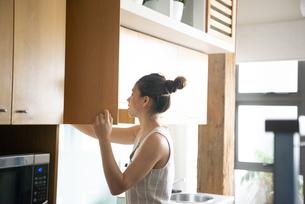 キッチンの扉を開けている女性の写真素材 [FYI03816473]