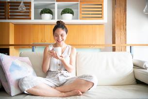 ソファでカップを持って笑っている女性の写真素材 [FYI03816641]