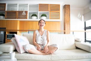 ソファで笑っている女性の写真素材 [FYI03816643]