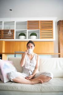 ソファで飲み物を飲んでいる女性の写真素材 [FYI03816719]