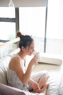 ソファで飲み物を飲んでいる女性の写真素材 [FYI03816732]