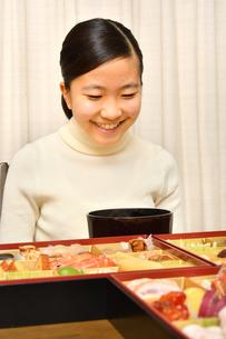 おせち料理を食べる女の子(正月)の写真素材 [FYI03817207]