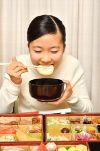 おせち料理を食べる女の子(正月)の写真素材 [FYI03817208]
