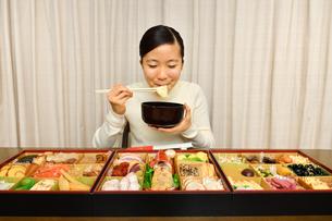 おせち料理を食べる女の子(正月)の写真素材 [FYI03817209]