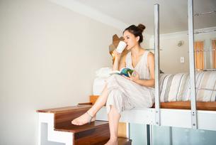 ロフトに座って飲み物を飲んでいる女性の写真素材 [FYI03817547]