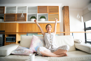 ソファの上で伸びをしている女性の写真素材 [FYI03817708]