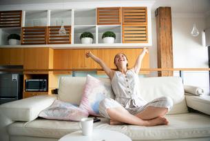 ソファの上で伸びをしている女性の写真素材 [FYI03817745]