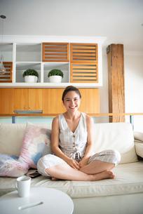 ソファの上であぐらをかいて笑っている女性の写真素材 [FYI03817755]