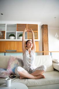 ソファの上で伸びをしている女性の写真素材 [FYI03817761]
