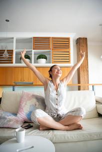 ソファの上で伸びをしている女性の写真素材 [FYI03817836]