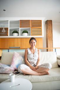 ソファの上であぐらをかいて笑っている女性の写真素材 [FYI03817837]