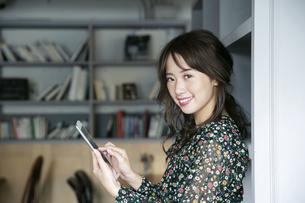 タブレットを操作する笑顔の20代女性の写真素材 [FYI03818109]