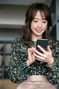 スマホを操作する笑顔の20代女性の写真素材 [FYI03818115]