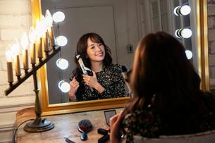 髪の毛を巻く笑顔の20代女性の写真素材 [FYI03818127]