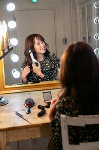 髪の毛を巻く笑顔の20代女性の写真素材 [FYI03818133]