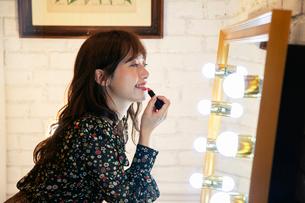 口紅を塗る笑顔の20代女性の写真素材 [FYI03818136]