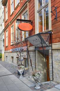 ラトビア・首都リガ新市街にある石壁と木製の外壁の建物の出入口前に飾られた鉢植えの写真素材 [FYI03818181]