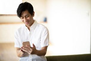スマートフォンを見る男性の写真素材 [FYI03818208]