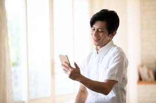 スマートフォンを見る男性の写真素材 [FYI03818211]