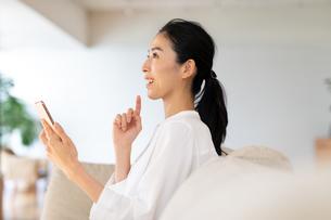 スマートホンを手に考える女性の写真素材 [FYI03818214]