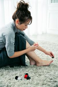 部屋で足のネイルを塗る20代女性の写真素材 [FYI03818472]