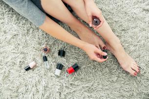 部屋で足のネイルを塗る女性の写真素材 [FYI03818474]