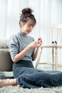 部屋で爪にネイルを塗る20代女性の写真素材 [FYI03818481]