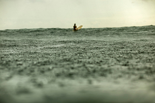 Distant view of woman surfing in sea during rainy seasonの写真素材 [FYI03818550]