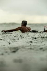 Man surfing in sea against sky during rainy seasonの写真素材 [FYI03818551]