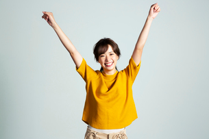 両腕を上げる笑顔の20代女性の写真素材 [FYI03818594]