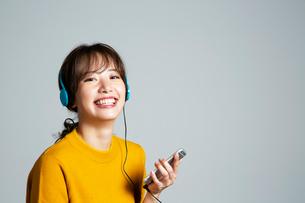 音楽を楽しむカメラ目線の20代女性の写真素材 [FYI03818747]