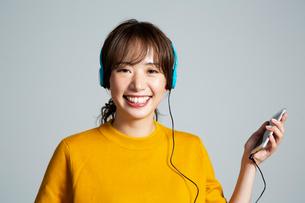 音楽を楽しむカメラ目線の20代女性の写真素材 [FYI03818753]