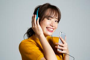 スマホを持ち音楽を楽しむ笑顔の20代女性の写真素材 [FYI03818781]