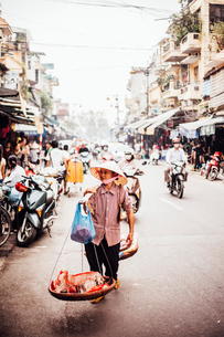 Woman selling fish while carrying baskets on shoulderの写真素材 [FYI03819131]