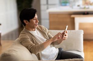 スマートフォンを操作する男性の写真素材 [FYI03819745]