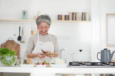 キッチンで料理する女性の写真素材 [FYI03820186]
