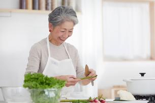 キッチンで料理する女性の写真素材 [FYI03820193]
