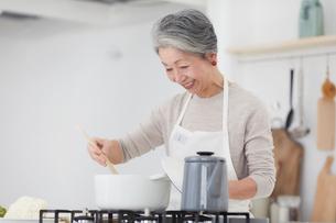 キッチンで料理する女性の写真素材 [FYI03820208]