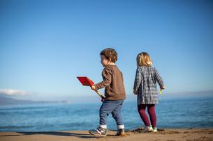 砂浜で遊ぶ男の子と女の子の後ろ姿の写真素材 [FYI03820219]