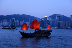 薄暮の香港のビクトリア湾を航行するジャンク型観光船「アクアルナ」の写真素材 [FYI03821985]