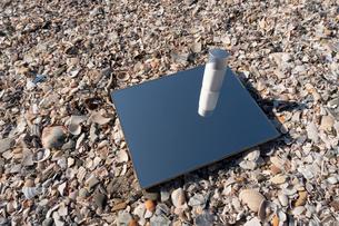 砂浜に鏡と日焼け止めの写真素材 [FYI03822737]