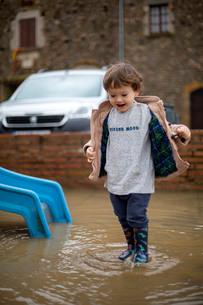 大きな水たまりで遊ぶハーフの幼児の写真素材 [FYI03822997]
